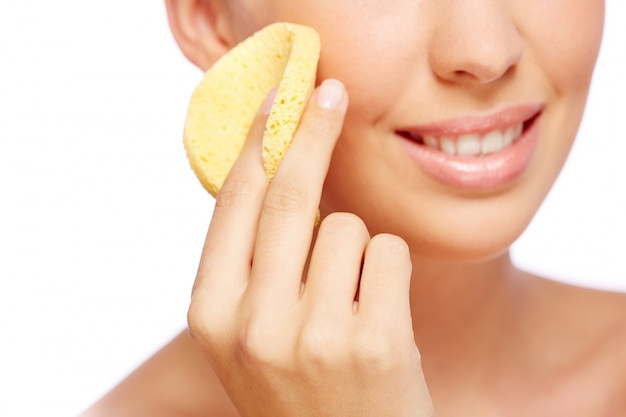 Close-up de uma mulher com uma esponja no rosto