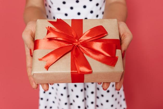 Close-up de uma mulher com vestido de bolinhas, mostrando a caixa de presente isolada
