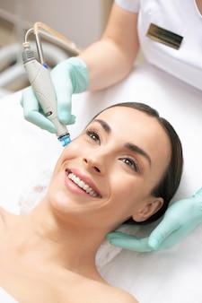 Close-up de uma mulher de cabelos escuros positiva sorrindo e tendo dermoabrasão da pele do rosto em uma clínica profissional