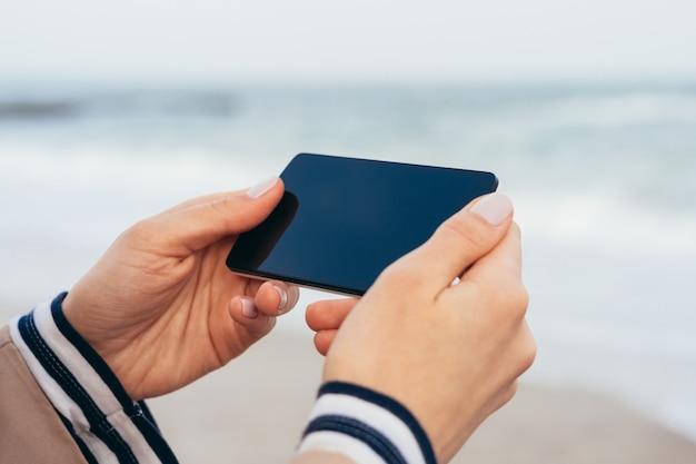 Close up de uma mulher de casaco bege na praia olhando para a tela do telefone inteligente