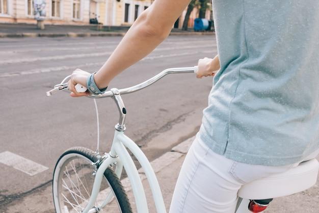 Close-up de uma mulher de esportes em uma bicicleta em uma cidade