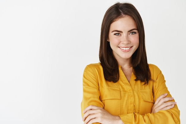 Close-up de uma mulher de negócios jovem profissional sorrindo para a câmera, cruzando os braços no peito e parecendo confiante, em pé sobre uma parede branca