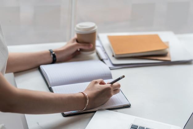 Close-up de uma mulher de negócios tomando notas e segurando café no escritório.