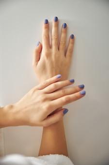 Close-up de uma mulher demonstrando dedos com unhas pintadas com esmalte de gel de cor isolado no fundo branco
