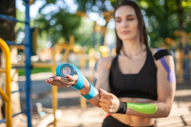 Close-up de uma mulher desfocada segurando rolos coloridos de fitas elásticas de cinesiologia