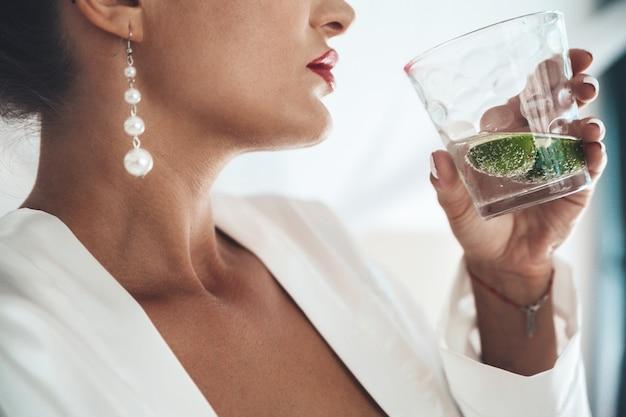 Close-up de uma mulher, desfrutando de um cocktail de mojito tropical decorado com frutas frescas nas férias de verão