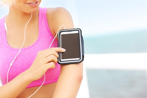Close-up de uma mulher em forma tocando o telefone colocado na braçadeira