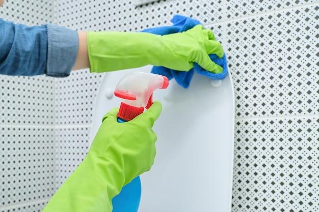 Close-up de uma mulher em luvas com pano e detergente para limpar o vaso sanitário, limpar a casa no banheiro
