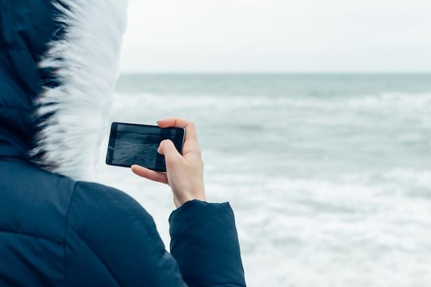 Close-up de uma mulher em uma jaqueta de inverno com capuz, usando um telefone celular na praia