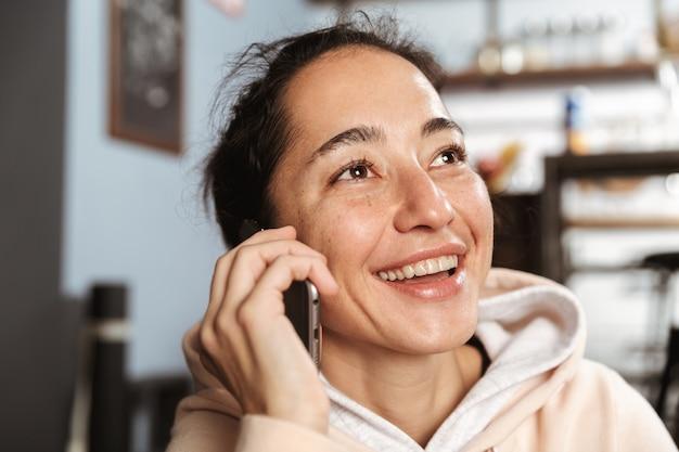 Close-up de uma mulher feliz falando no celular em casa