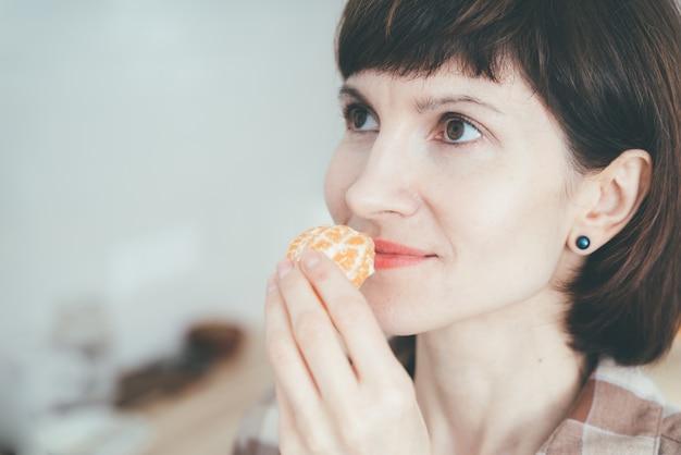 Close-up de uma mulher feliz inalando um mandarim