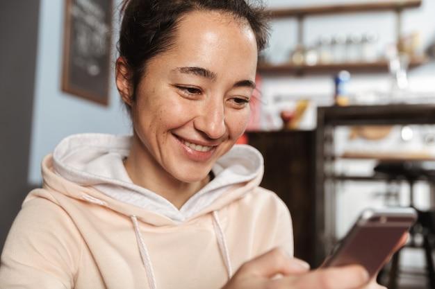Close-up de uma mulher feliz usando o celular em casa