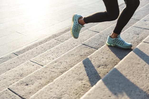 Close-up de uma mulher fitness subindo a escada correndo ao ar livre