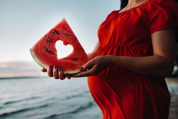 Close-up de uma mulher grávida segurando um pedaço de melancia com um coração feito com ela, em pé na natureza.