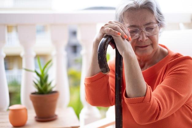Close-up de uma mulher idosa e melancólica, sofrendo de dor nas costas, sentada com as mãos apoiadas na bengala