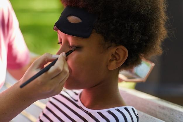 Close-up de uma mulher irreconhecível colocando maquiagem ou pintura facial em um garoto afro-americano usando fantasia de halloween