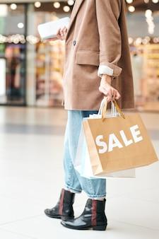 Close-up de uma mulher irreconhecível em uma jaqueta comprida, andando com sacolas de compras, enquanto aprecia uma grande promoção no shopping