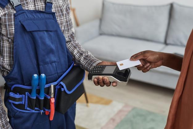 Close-up de uma mulher irreconhecível pagando faz-tudo por serviços passando o cartão no terminal do banco, copie o espaço