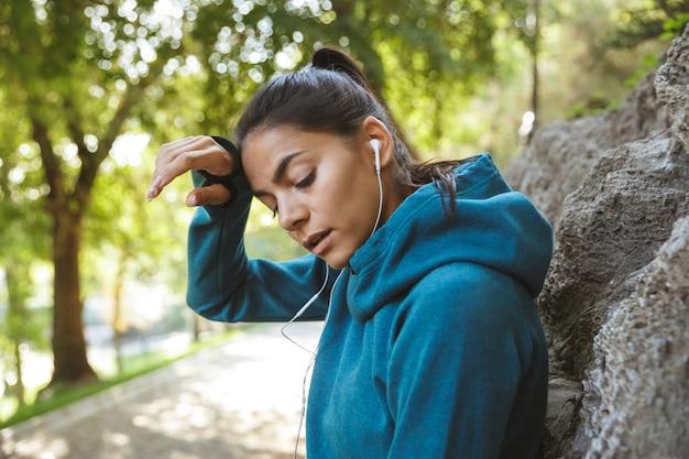 Close-up de uma mulher jovem e atraente fitness vestindo roupas esportivas, fazendo exercícios ao ar livre, descansando após o treino