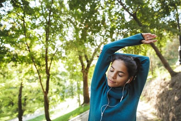 Close-up de uma mulher jovem e atraente fitness vestindo roupas esportivas, fazendo exercícios ao ar livre, fazendo exercícios de alongamento
