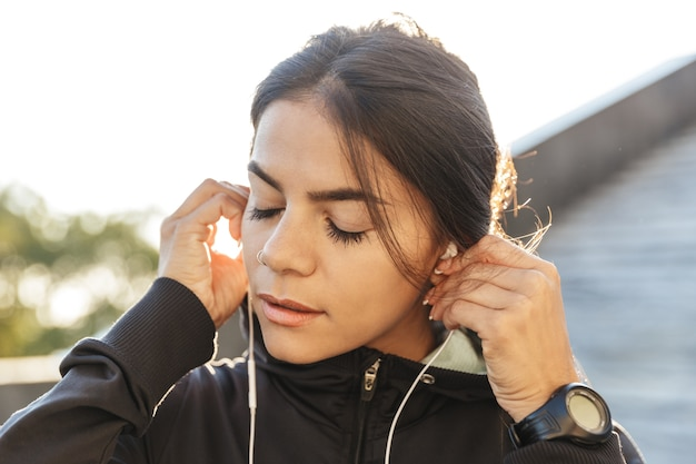 Close-up de uma mulher jovem e atraente fitness vestindo roupas esportivas, fazendo exercícios ao ar livre, ouvindo música com fones de ouvido