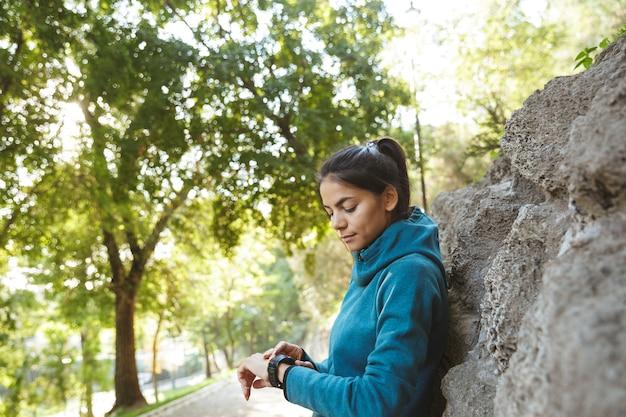 Close-up de uma mulher jovem e atraente fitness vestindo roupas esportivas, fazendo exercícios ao ar livre, usando smartwatch