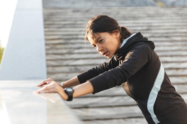Close-up de uma mulher jovem e atraente fitness vestindo roupas esportivas, fazendo exercícios ao ar livre