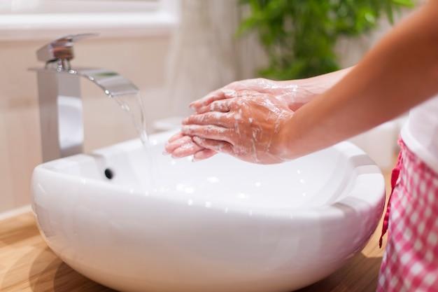 Close-up de uma mulher lavando as mãos no banheiro