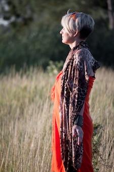 Close-up de uma mulher loira de meia idade em pé em um prado de frente para o sol e meditando.