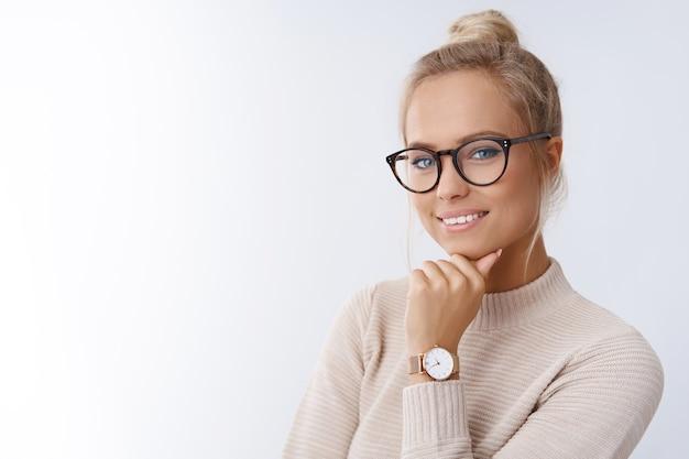 Close-up de uma mulher loira europeia atraente, feliz e bem-sucedida, sorrindo, com suéter e óculos, sorrindo, expressando confiança, parecendo competente e ousado para a câmera com um sorriso atrevido