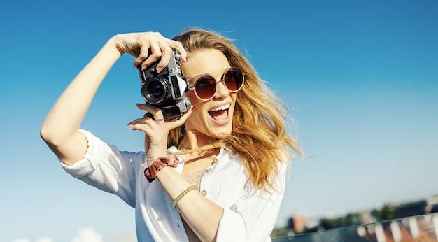 Close-up de uma mulher loira sorridente, vestida de maneira elegante, posando com uma câmera