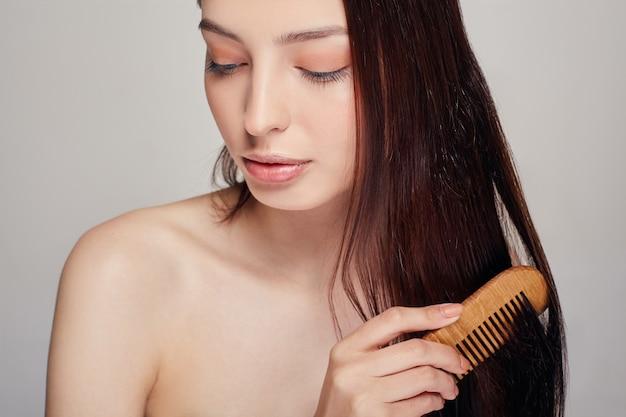 Close-up de uma mulher macia com um humor brincalhão penteia os cabelos com um pente marrom claro nos olhares longe, sem um leve sorriso