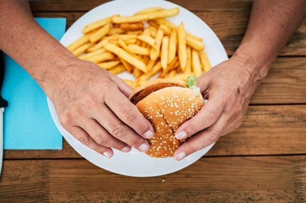 Close-up de uma mulher madura segurando um hambúrguer com batatas fritas em uma mesa de madeira - fast food e estilo de vida pouco saudável e conceito