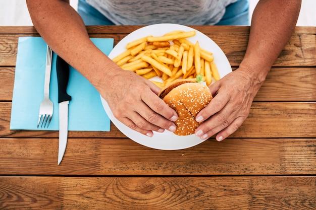 Close-up de uma mulher madura segurando um hambúrguer com batatas fritas em uma mesa de madeira - fast food e estilo de vida pouco saudável
