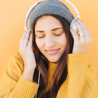 Close-up de uma mulher ouvindo música em fones de ouvido com os olhos fechados