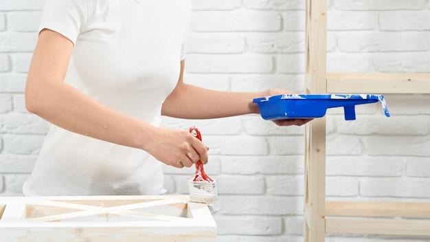 Close-up de uma mulher pintando prateleiras de madeira com a cor branca