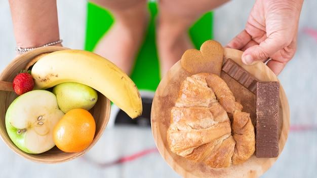 Close-up de uma mulher segurando em pratos com dois tipos diferentes de alimentos - alimentos não saudáveis e saudáveis - pessoa em uma balança de peso ao fundo