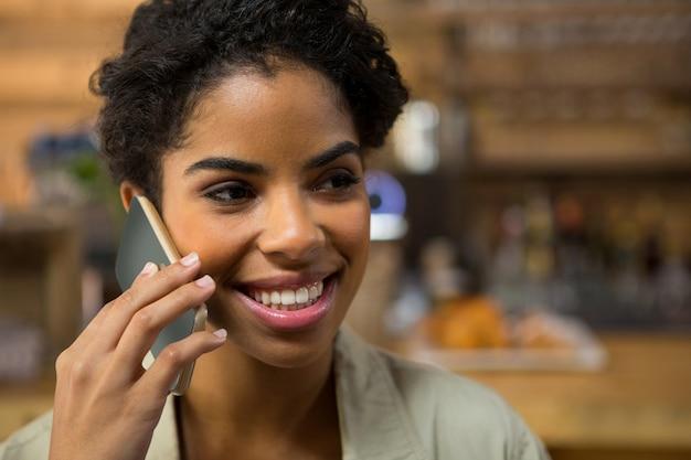 Close-up de uma mulher sorridente falando no telefone inteligente em uma cafeteria