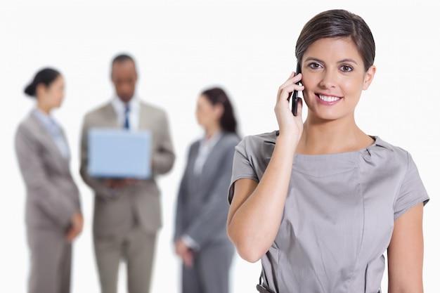 Close-up de uma mulher sorrindo no telefone e colegas de trabalho com um laptop