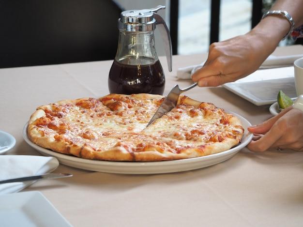 Close-up de uma mulher tomando um pedaço de pizza em um restaurante