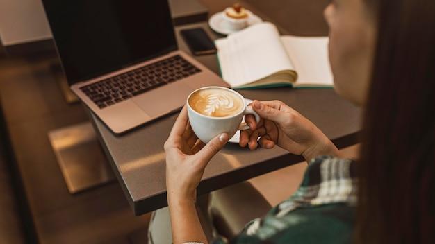Close-up de uma mulher tomando uma xícara de café