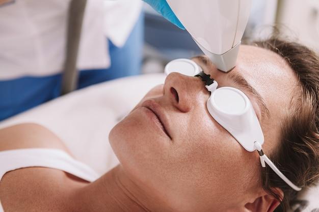 Close-up de uma mulher usando óculos de proteção, obtendo os pêlos faciais removidos pela esteticista