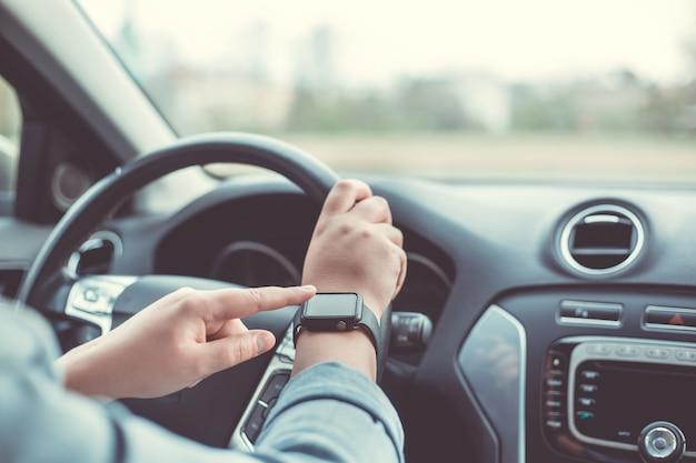 Close-up de uma mulher usando relógio inteligente durante a condução do carro dela, conceito de transporte