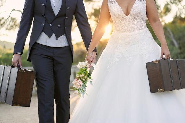Close-up de uma noiva e do noivo carregando malas para a lua de mel.