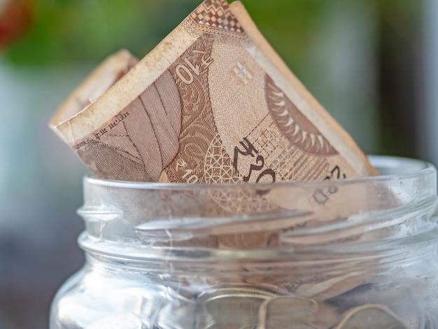 Close-up de uma nota de rúpia indiana em uma jarra de vidro cheia de moedas. o conceito de economia de dinheiro, investimentos. foco seletivo