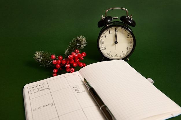 Close-up de uma página aberta de caderno, agenda com planos para o dia, despertador e ramo nevado da planta de natal de azevinho isolada em fundo verde