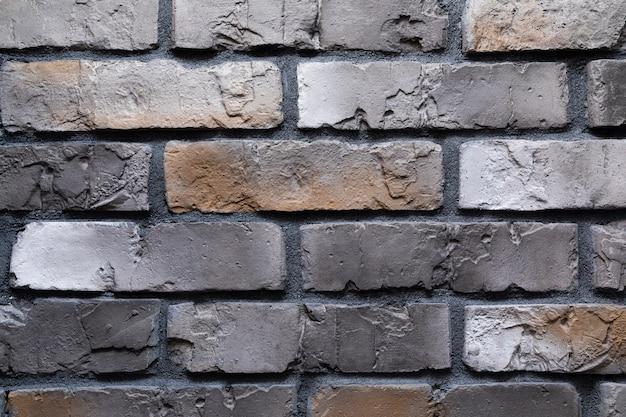Close-up de uma parede de tijolos de grafite marrom com manchas marrons