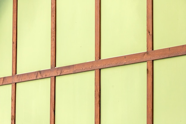 Close-up de uma parede verde de uma casa de madeira com barras marrons.