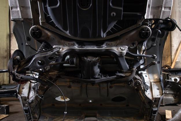 Close-up de uma parte da carroceria de um carro antigo serrada: parte inferior do corpo, suspensão traseira com múltiplas ligações, freios a disco, braços de suspensão, tubos de freio em uma garagem antiga. analisando jankyard