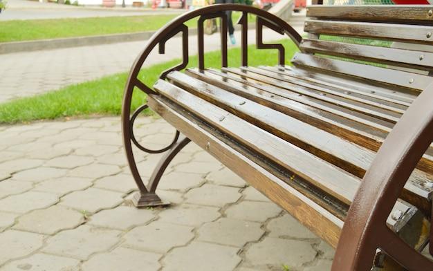 Close-up de uma parte de um novo banco de madeira marrom com corrimãos de metal, ao ar livre
